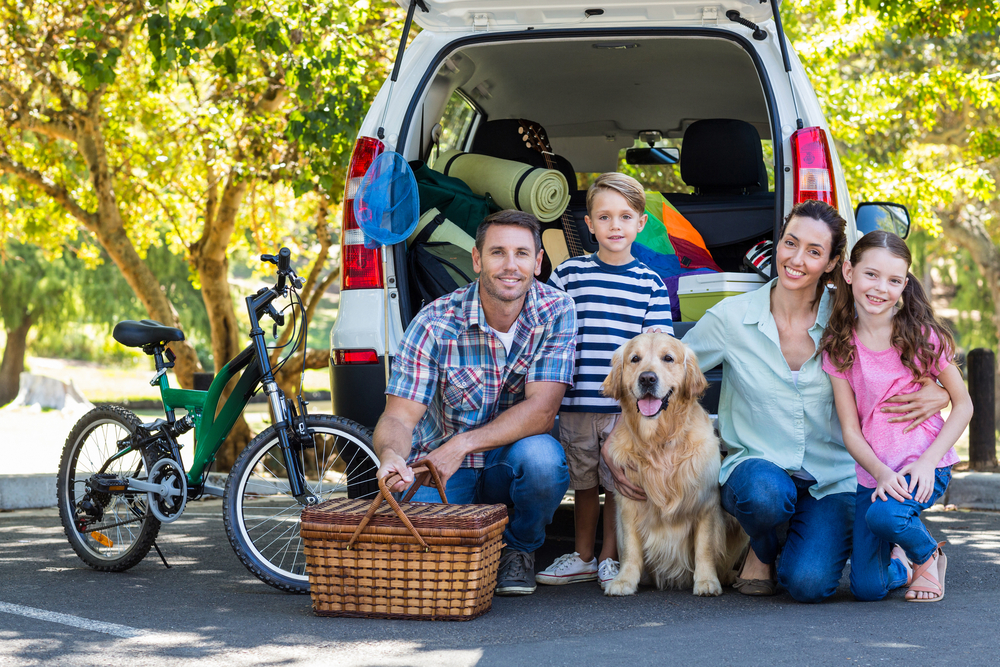 Family packing car for summer road trip.